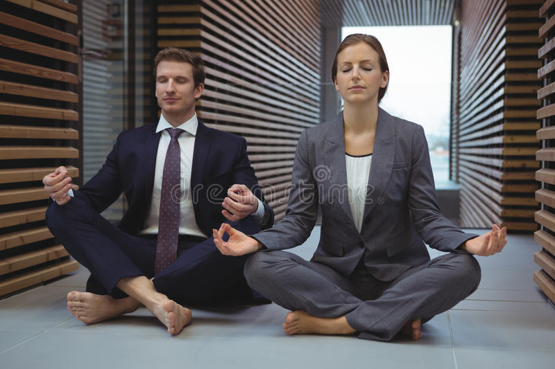 Businesspeople performing yoga in the corridor royalty free stock image