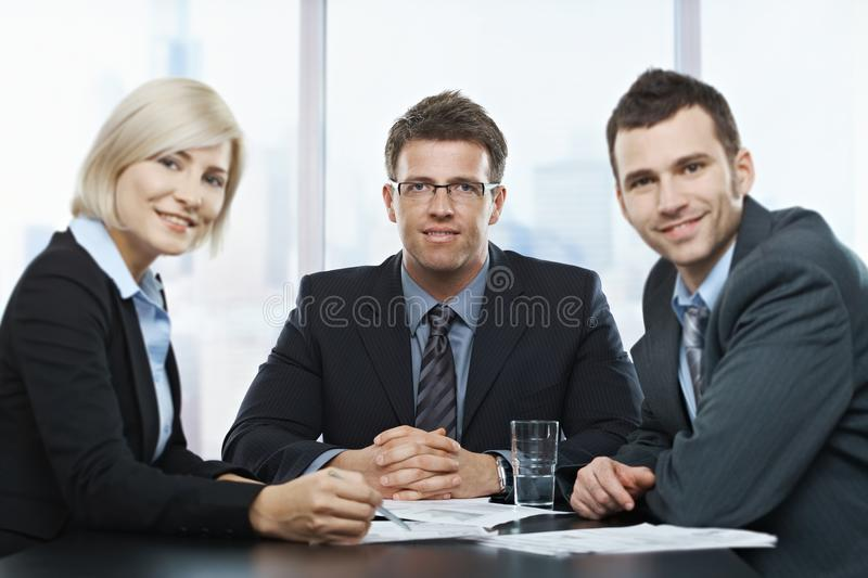 Businesspeople portrait. Portrait of businesspeople at office meeting looking at camera sitting at table royalty free stock images