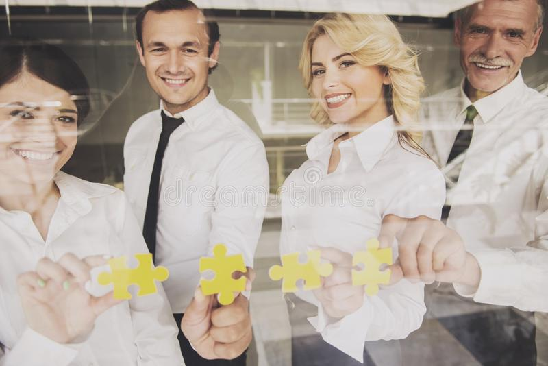 Businesspeople Put Pieces of Puzzle on Glass Door. stock photos