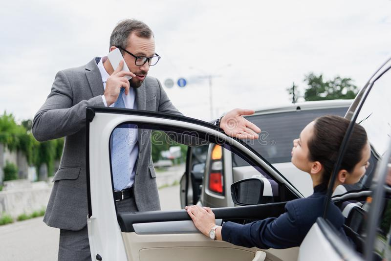 Businesspeople quarreling on road after car accident man. Talking by smartphone royalty free stock image