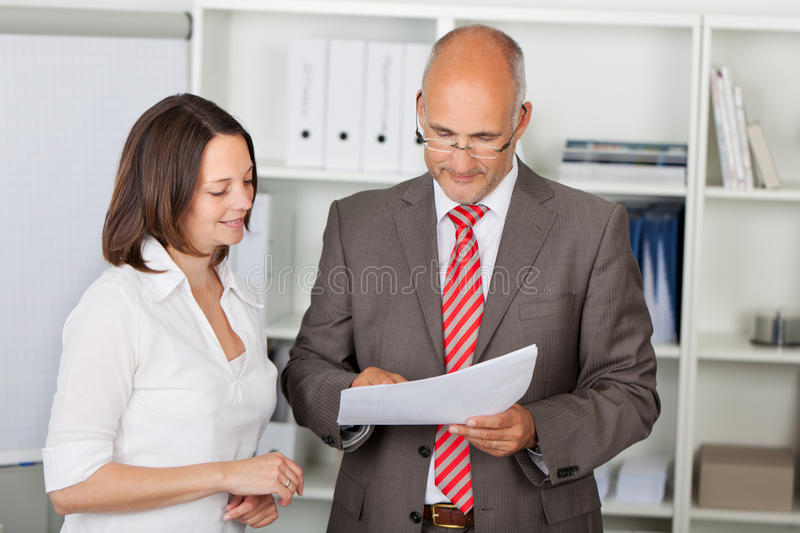 Businesspeople Reading Document In Office royalty free stock images