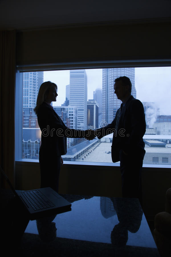 Businesspeople Shaking Hands. Silhouette of a businessman and businesswoman shaking hands. The city can be seen through the window in the background. Vertical royalty free stock photography