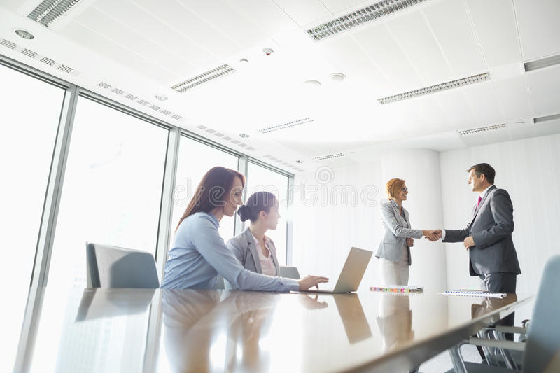 Businesspeople shaking hands in board room stock photos