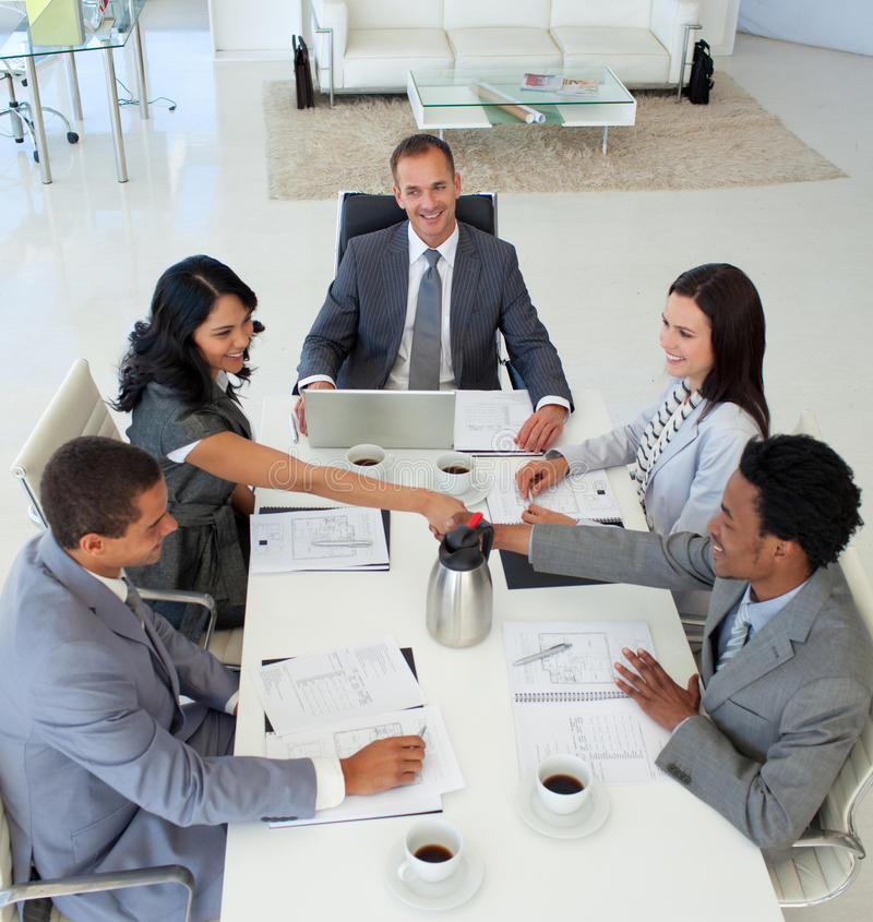 Businesspeople shaking hands in a meeting. High angle of businesswoman and businessman shaking hands in a meeting royalty free stock image