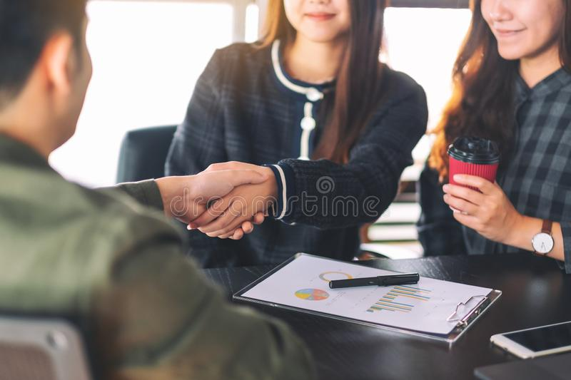 Businesspeople shaking hands in a meeting. Closeup image of businesspeople shaking hands in a meeting stock image