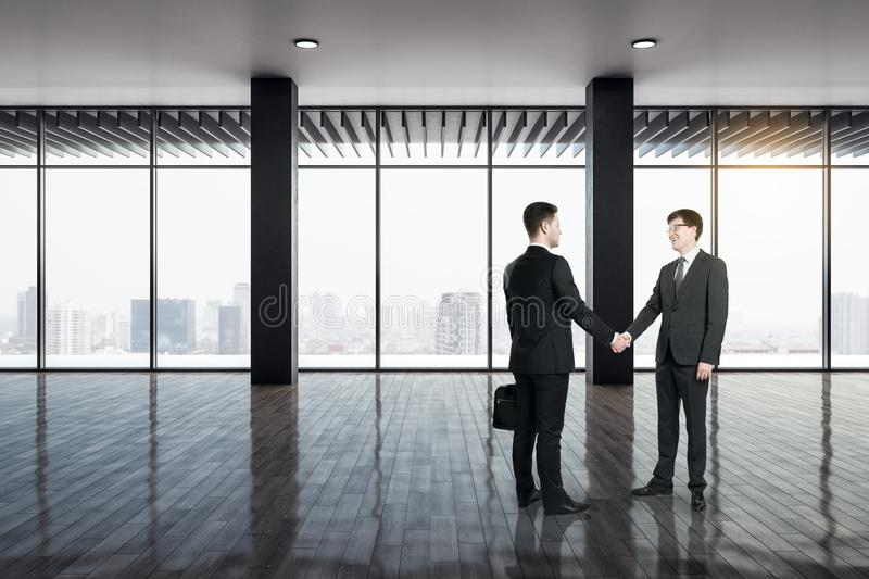Team and success concept. Businesspeople shaking hands in modern office interior with city view and daylight. Team and success concept stock photography