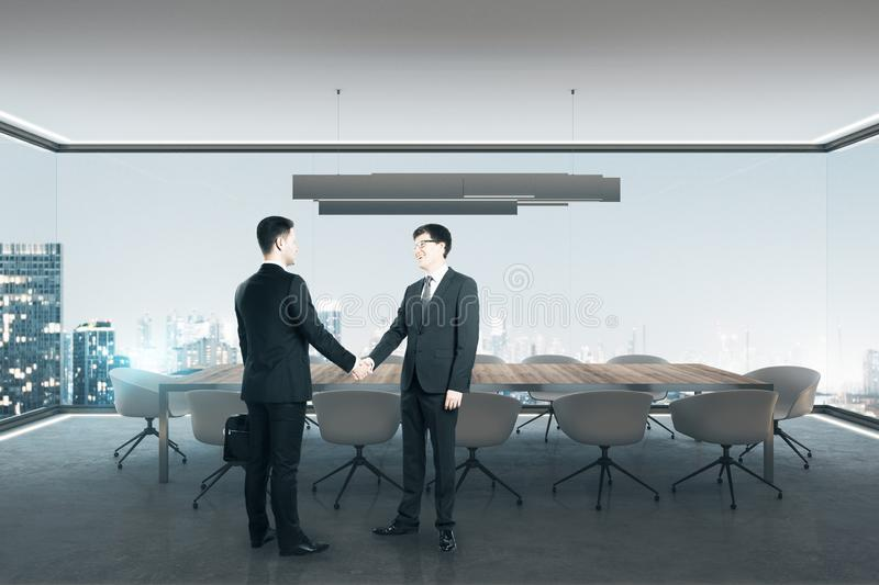 Businesspeople shaking hands in office. Businesspeople shaking hands looking out of window in modern spacious meeting room interior with illuminated panoramic stock images