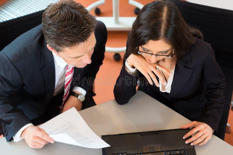 Businesspeople sitter på kontorsskrivbordet royaltyfria foton