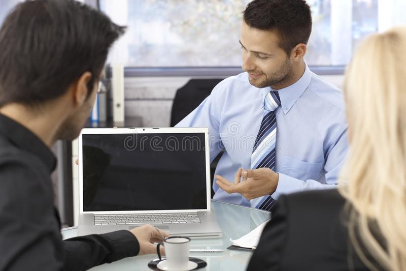 Businesspeople sitting around laptop computer royalty free stock photo