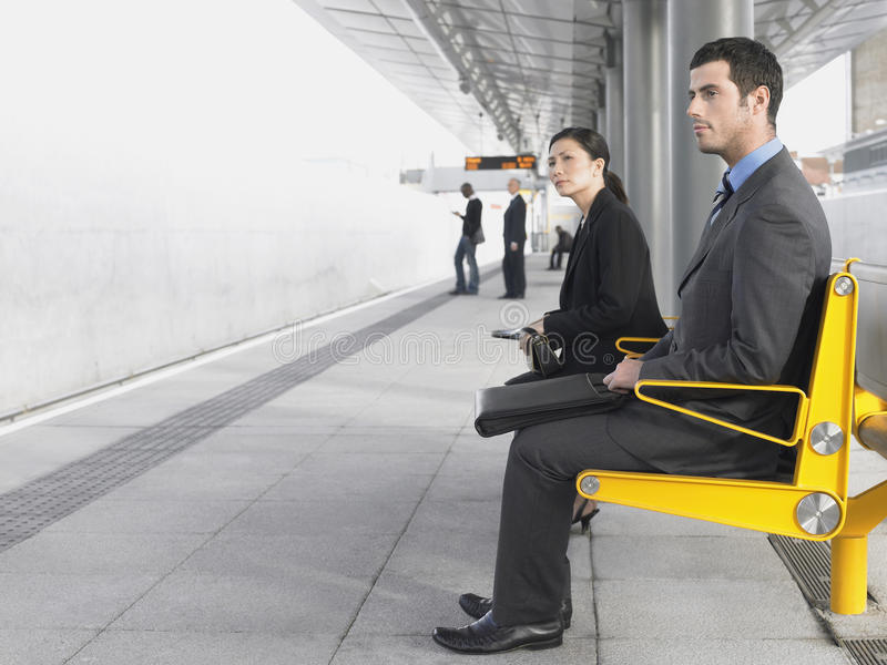 Businesspeople Sitting On Train Station Bench. Side view of businesspeople sitting on bench waiting at train station royalty free stock image