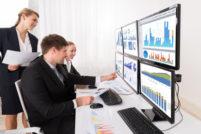 Businesspeople som analyserar grafer på åtskilliga datorer royaltyfria bilder