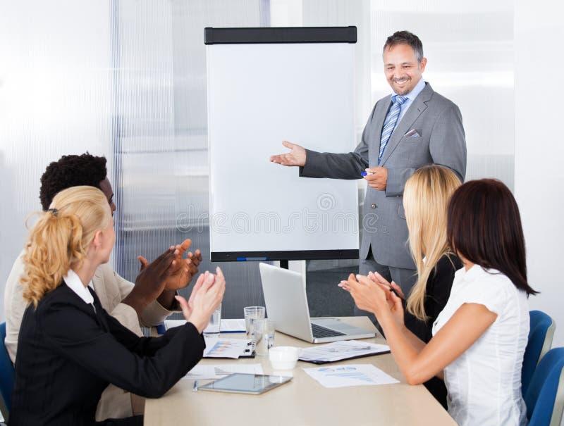 Businesspeople som applåderar för en man i möte royaltyfria bilder