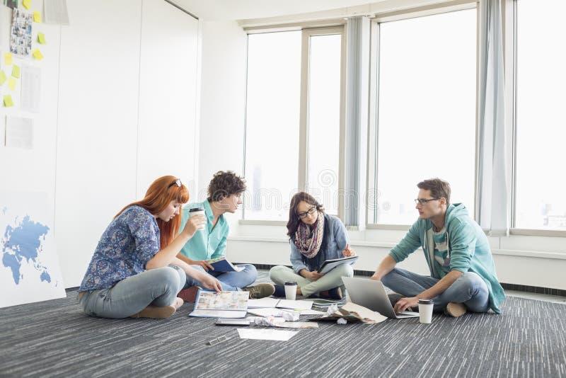 Businesspeople som arbetar på golv på utrymme för idérikt arbete arkivbild