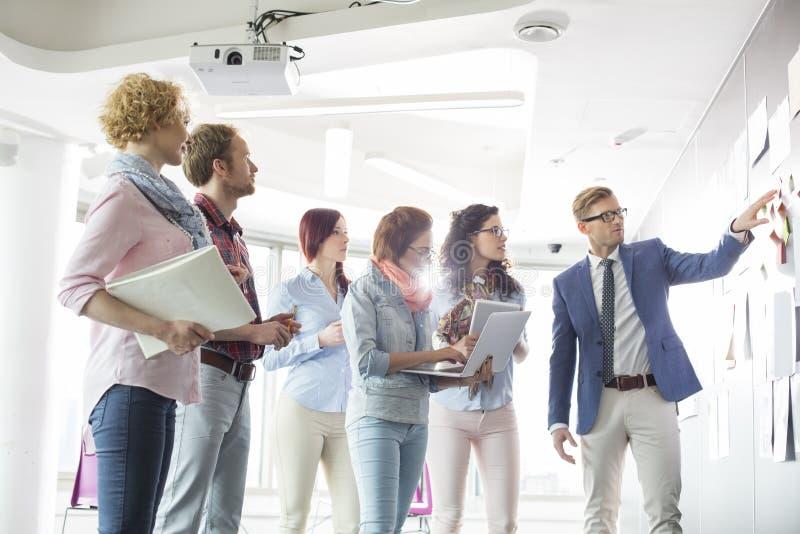 Businesspeople som diskuterar över dokument på väggen i idérikt kontor arkivfoto