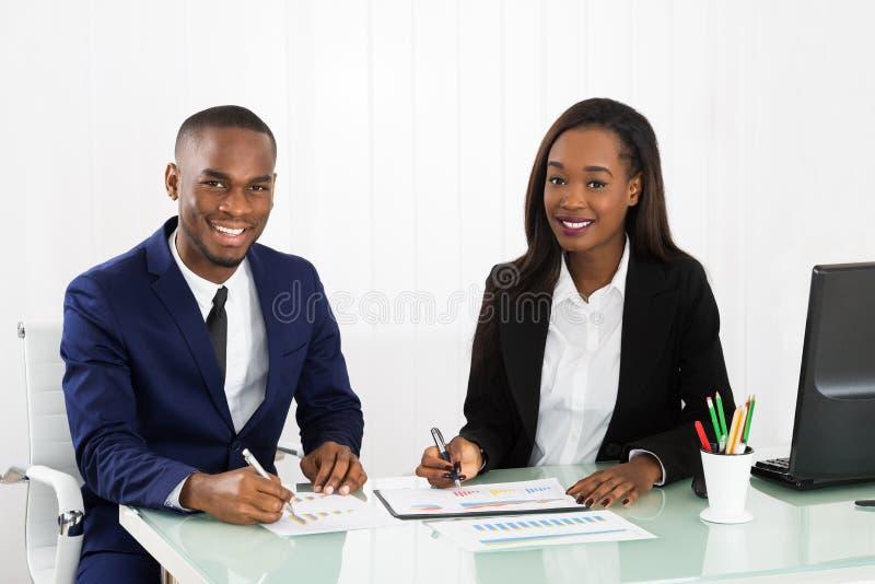 Businesspeople som diskuterar diagrammen och graferna royaltyfri foto