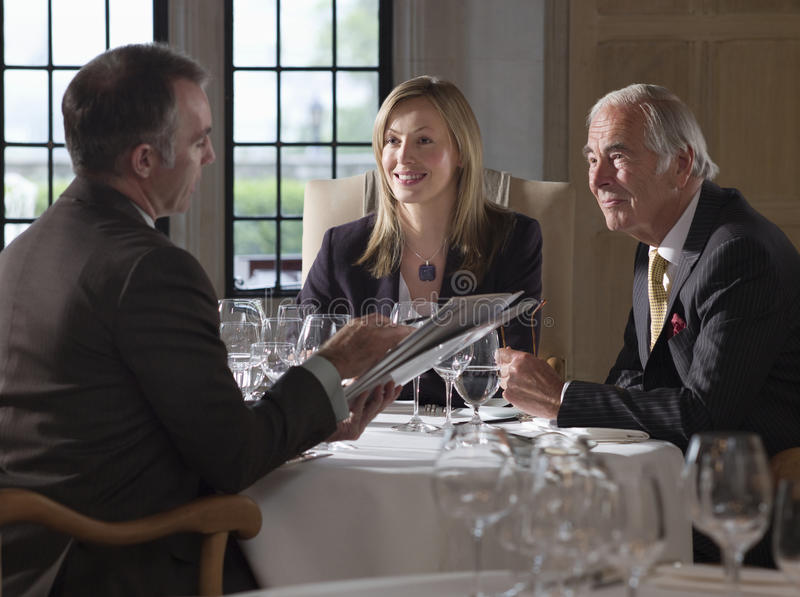 Businesspeople som diskuterar dokument på restaurangtabellen royaltyfri fotografi