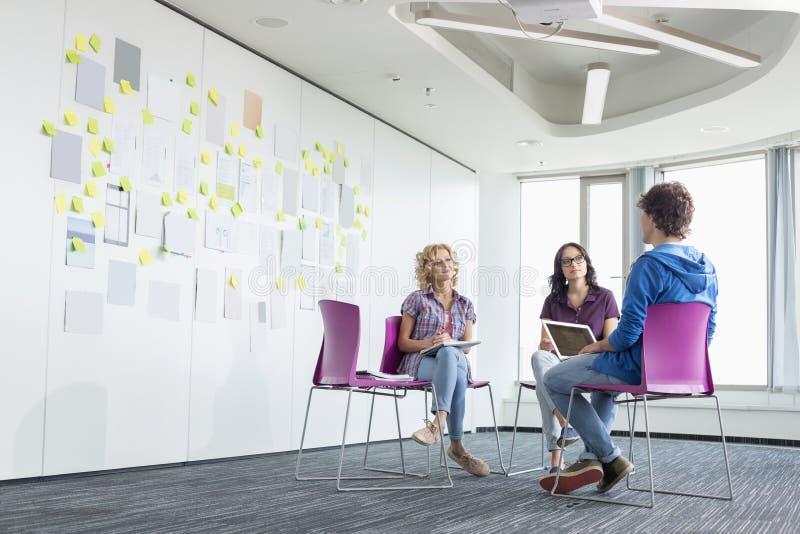 Businesspeople som diskuterar i idérikt kontorsutrymme arkivfoto
