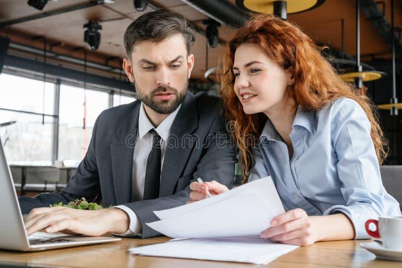 Businesspeople som har affärslunch på den sittande mannen för restaurang som bläddrar bärbara datorn som ser kvinnainnehavavtalet royaltyfria bilder