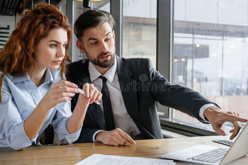 Businesspeople som har affärslunch på den sittande mannen för restaurang som frågar kvinnafrågan som pekar på bärbara datorn arkivbilder