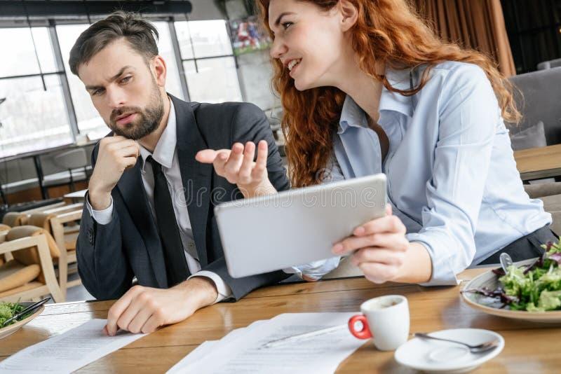 Businesspeople som har affärslunch på för kvinnavisning för restaurang den sittande idén på den digitala minnestavlan medan se fö royaltyfria foton