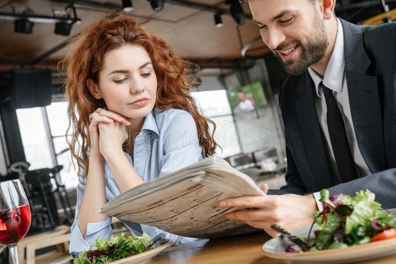 Businesspeople som har affärslunch på restaurangen som sitter äta sallad som dricker den koncentrerade vinläsningtidningen arkivfoto