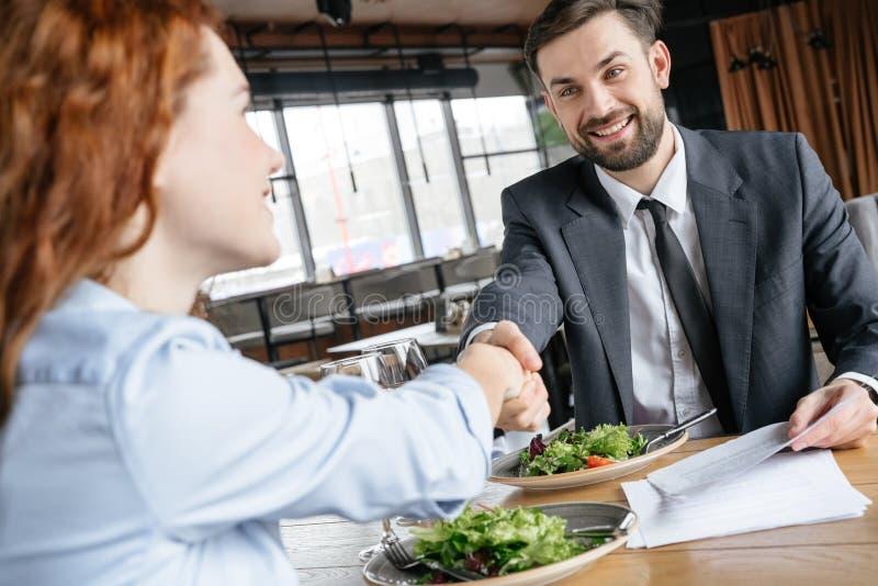 Businesspeople som har affärslunch på restaurangen som sitter äta sallad som dricker vin som skakar händer som gör avtal lyckligt royaltyfri fotografi