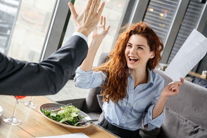 Businesspeople som har affärslunch på restaurangen som sitter äta sallad som dricker vinkvinnanärbilden som ger fem till royaltyfri foto
