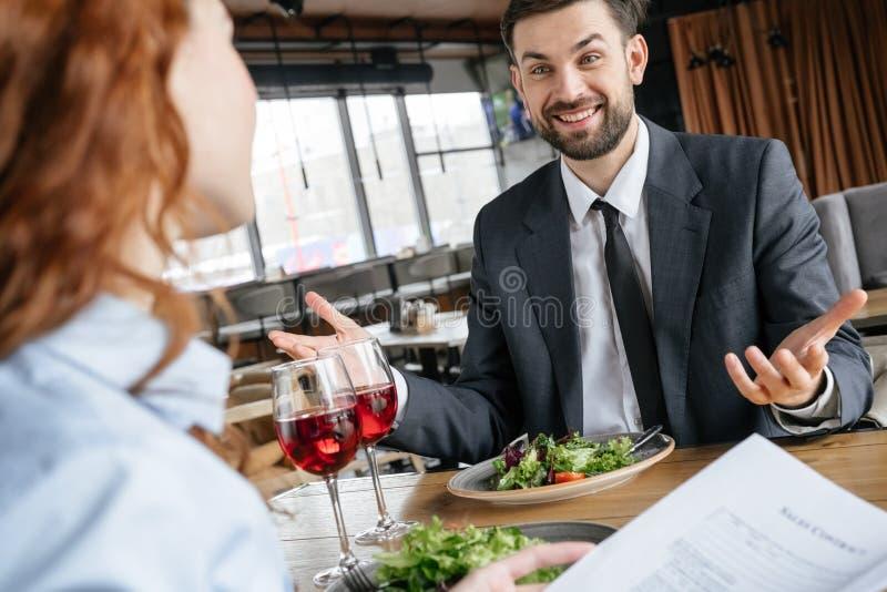 Businesspeople som har affärslunch på restaurangen som sitter äta sallad som dricker vinmannen som förklarar till kvinnaämnet royaltyfria foton