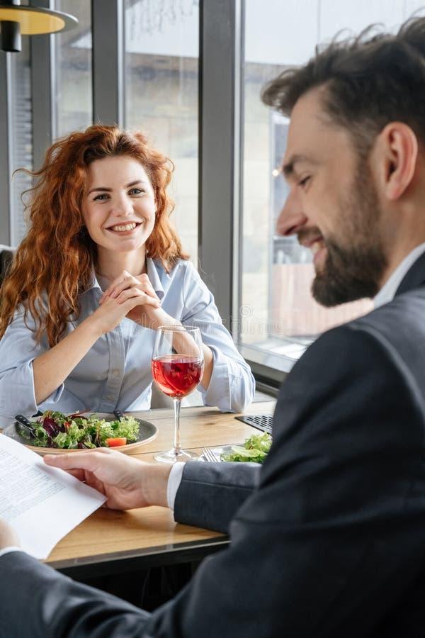 Businesspeople som har affärslunch på restaurangen som sitter äta sallad som dricker vinmannen som läser avtalet som ler stund arkivfoton