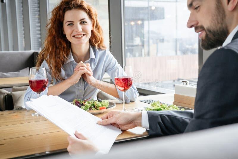 Businesspeople som har affärslunch på restaurangen som sitter äta sallad som dricker vinmannen som läser dokument medan kvinna royaltyfri foto