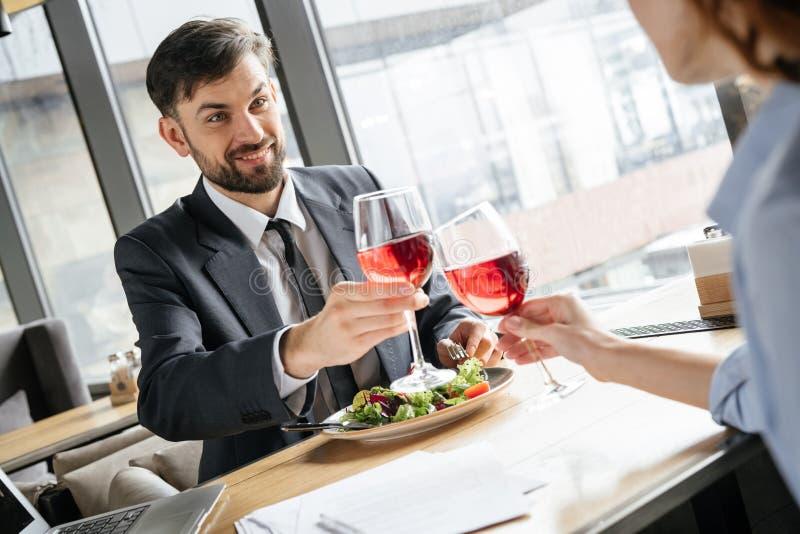 Businesspeople som har affärslunch på restaurangen som sitter nära fönstret som dricker att le för vin som är lyckligt royaltyfri foto