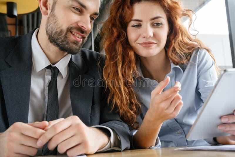 Businesspeople som har affärslunch på restaurangen som sitter se digitalt le för minnestavla royaltyfria bilder
