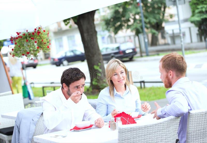 Businesspeople som har mat på den utomhus- restaurangen royaltyfri fotografi