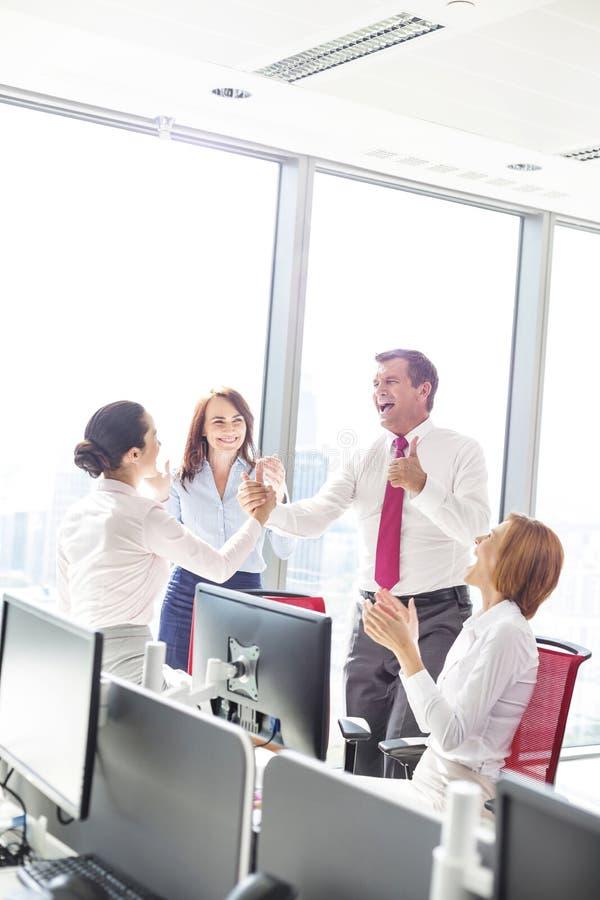 Businesspeople som i regeringsställning firar framgång royaltyfri bild