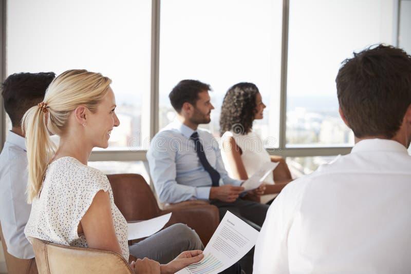 Businesspeople som i regeringsställning lyssnar till presentationen royaltyfri bild