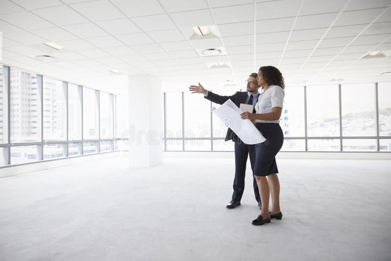 Businesspeople som möter för att se plan i tomt kontor fotografering för bildbyråer
