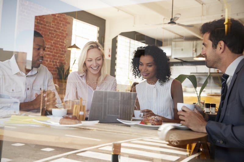 Businesspeople som möter i coffee shop som skjutas till och med fönster fotografering för bildbyråer