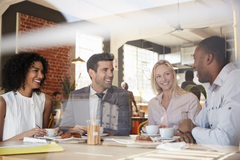 Businesspeople som möter i coffee shop som skjutas till och med fönster arkivbild