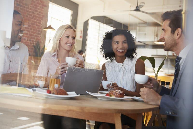 Businesspeople som möter i coffee shop som skjutas till och med fönster royaltyfria bilder