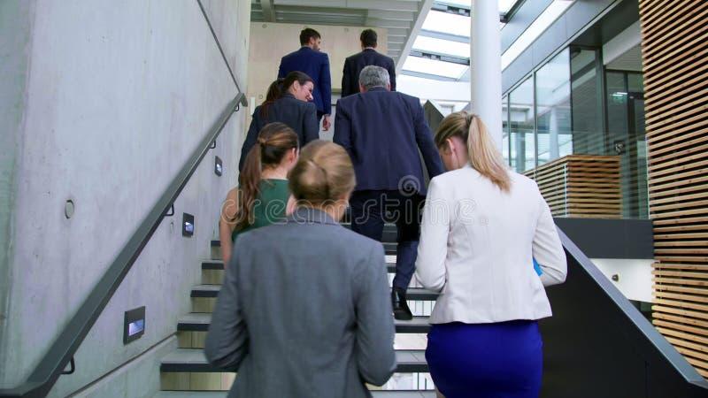 Businesspeople som påverkar varandra med de, medan gå på trappa arkivfilmer