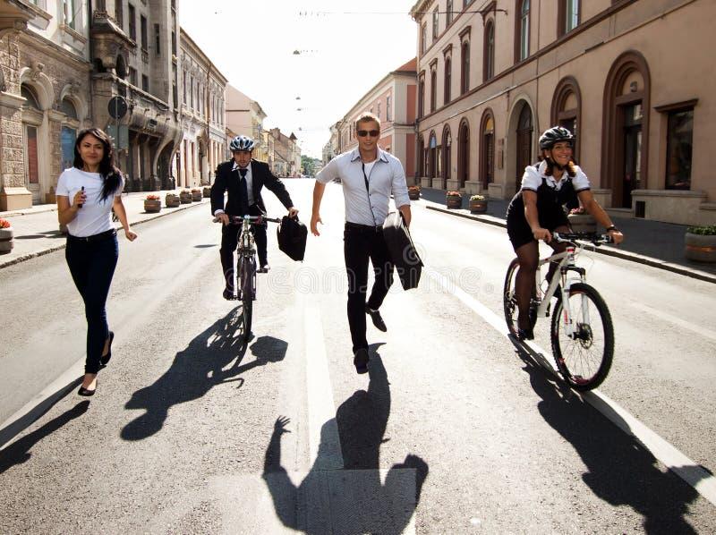 Businesspeople som rider på cyklar och running arkivbild