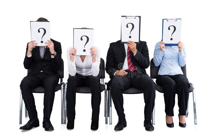Businesspeople som rymmer tecknet för frågefläck arkivfoto