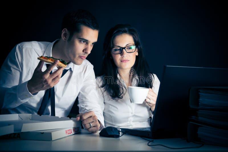Businesspeople som sent arbetar arkivfoto
