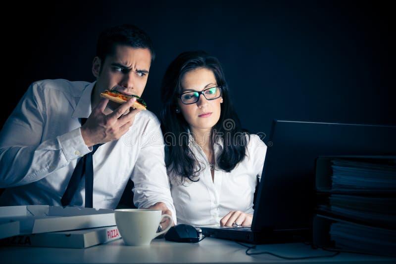 Businesspeople som sent arbetar arkivbild