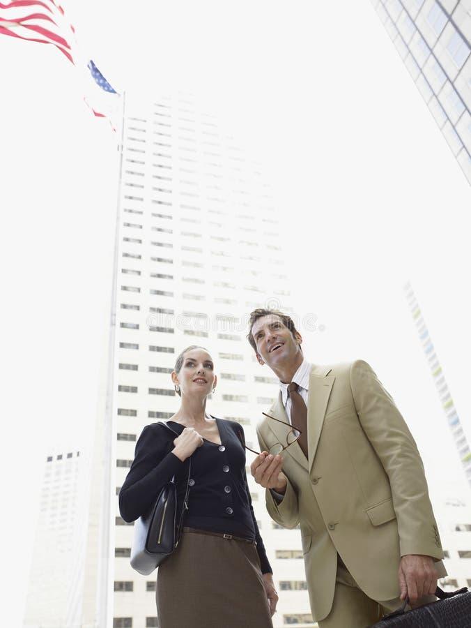 Businesspeople som ser bort mot kontorsbyggnad royaltyfria bilder