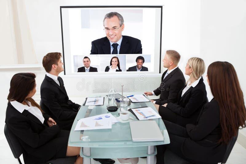 Businesspeople som ser projektorskärmen arkivfoton