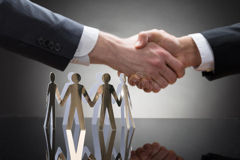 Businesspeople som skakar händer med pappers- diagram royaltyfri bild