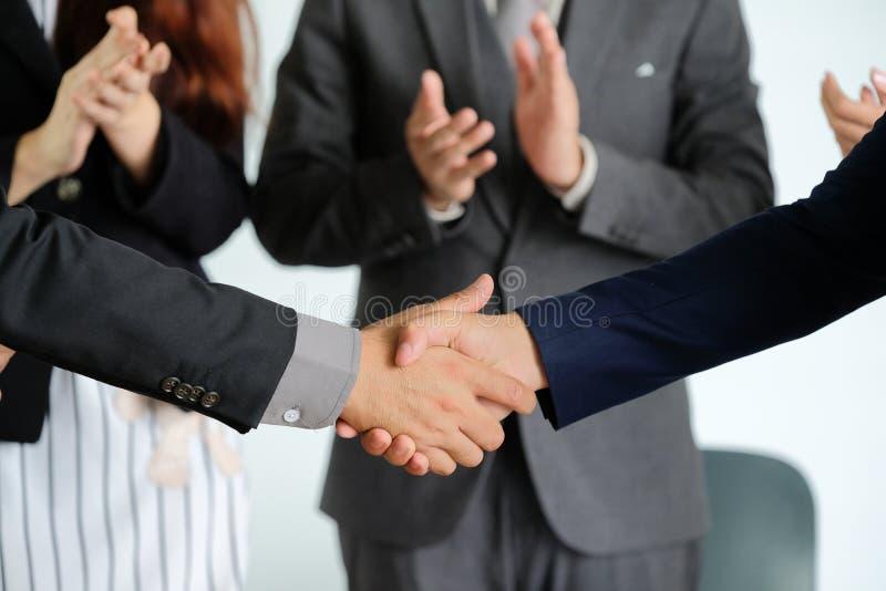 Businesspeople som skakar händer mot rum royaltyfria foton
