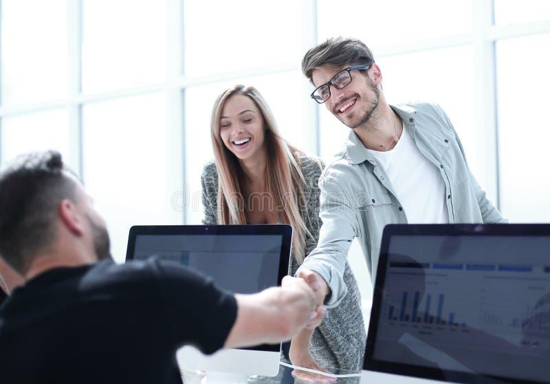 Businesspeople som skakar händer mot rum med den stora fönsterlooen arkivfoto
