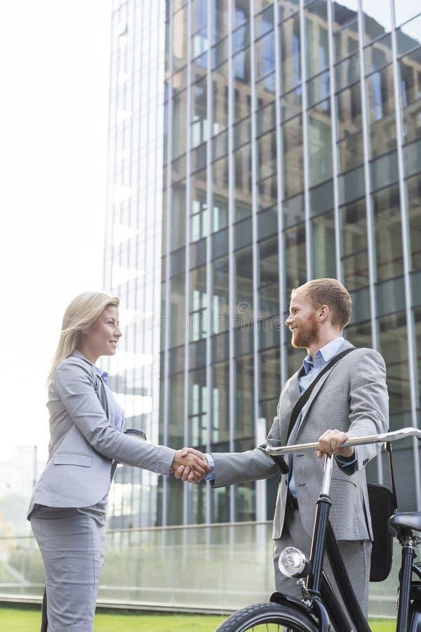 Businesspeople som skakar händer utanför kontorsbyggnad arkivfoto